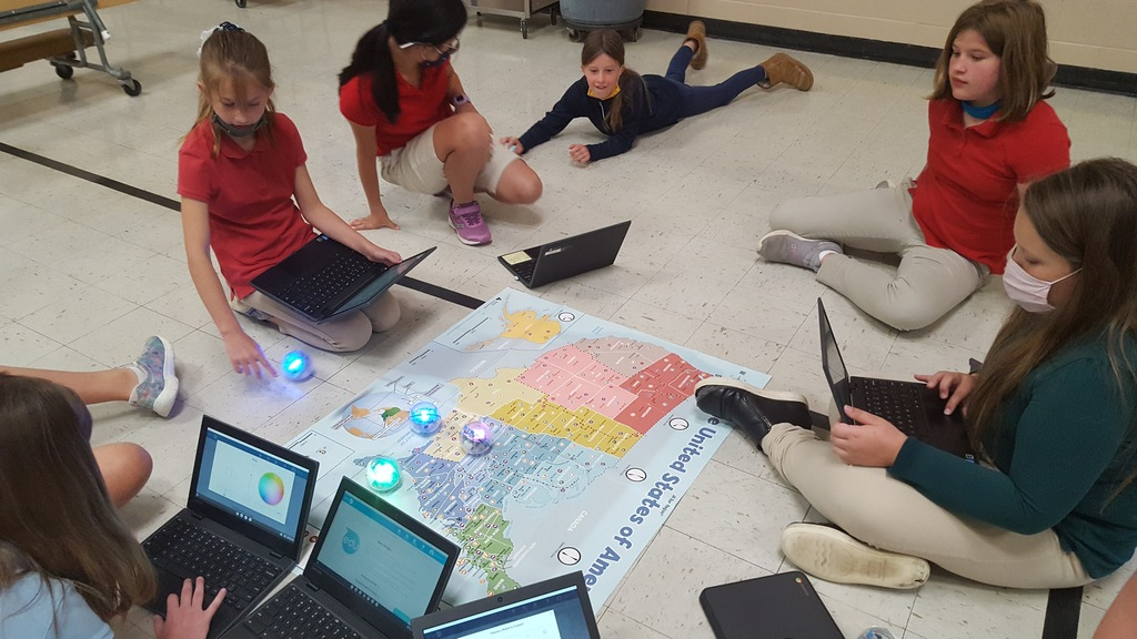 Fourth graders with US map and robots