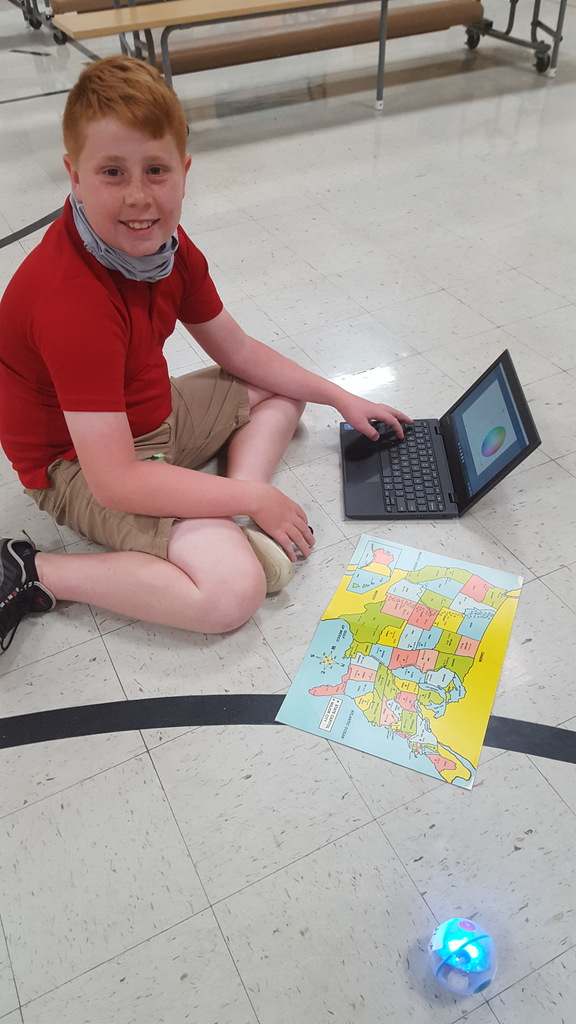 Fourth grade boy with robot, computer and US map.